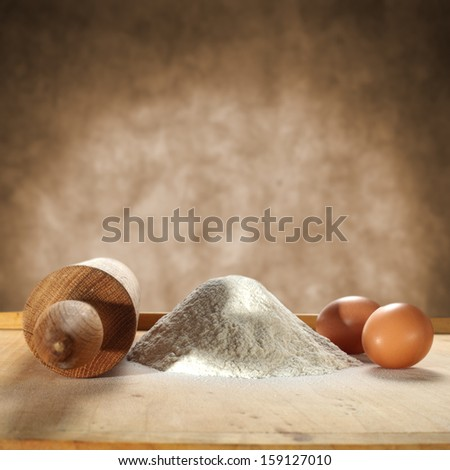 brown background of eggs and white flour  - stock photo