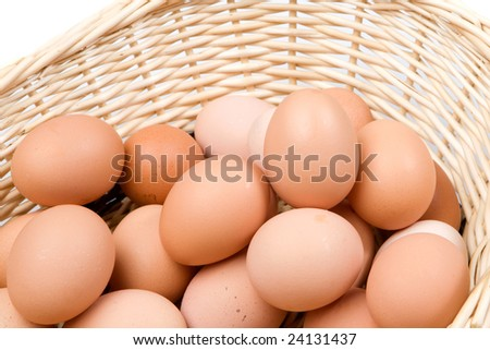 Brown basket with a lot of hen eggs isolated over white