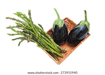 Brown basket with bunch of asparagus and two aubergines isolated on white background - stock photo