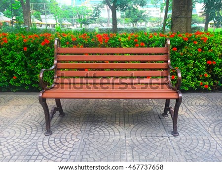 Brown bench in inside garden which having bush and tree as background