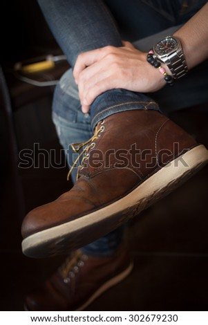brown boot leather shoes and jean pants clothing fashion of man
