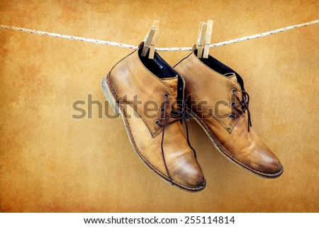 Brown boots hanging on rope over brown background - stock photo