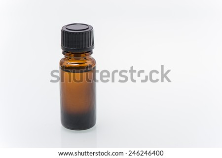 Brown bottle with medicine on a white background is beside the lid and a spoon. isolated