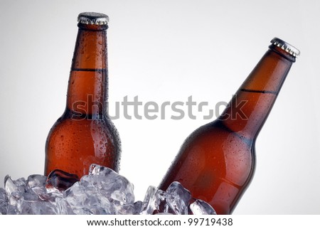 brown bottles of beer chilling on ice - stock photo