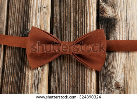 Brown bow tie on a brown wooden table - stock photo