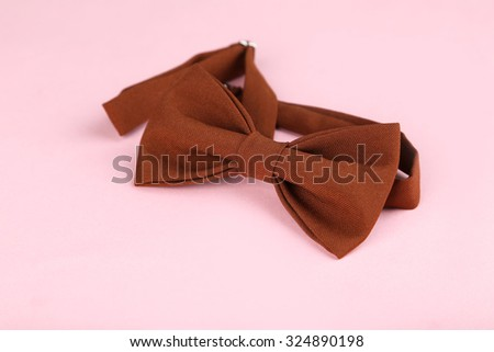 Brown bow tie on a pink background - stock photo