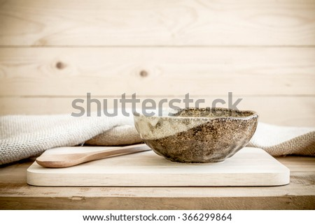 Brown bowl with spoon on wooden background.