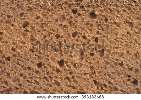 Brown bread background, bread texture pattern, detailed look at the rye porous brown bread slice, bread macro view - stock photo