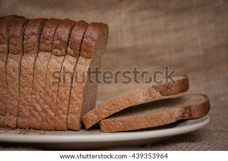 Brown bread loaf cut into slices on a gunny sack background