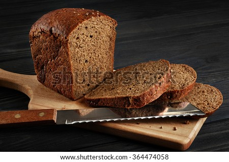 Brown bread on a dark background. Bread knife. - stock photo