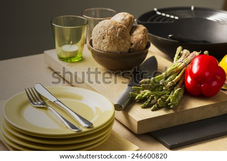 Brown Bread on Bowl, Fresh Veggies, Cutting Knife, Glass with Candles and Plates with Fork and Knife on top of Table. Preparing for Meal. - stock photo