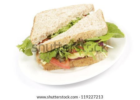 Brown bread sandwich with fresh tomato and lettuce on a white plate with a plain background