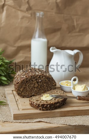 Brown bread with sunflower seeds with butter on the wooden table