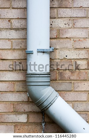 Brown brick wall with grey gutter or drain pipe. - stock photo