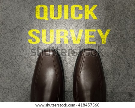 Brown business shoes on floor with text:Quick survey - stock photo