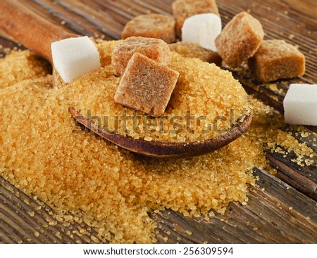 Brown cane sugar on   wooden board. Selective focus - stock photo