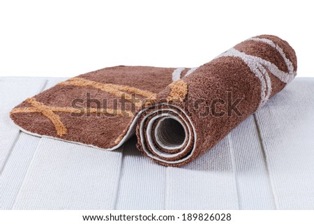 brown carpet rolled up on white carpet  - stock photo