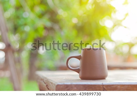 brown ceramic coffee cup with blur green garden background and soft light effect