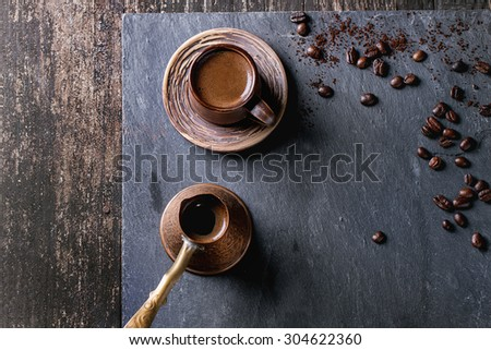 Brown ceramic cup of coffee, old copper cezve and coffee beans. Over black slate as background. With copy space at centre. Top view. - stock photo