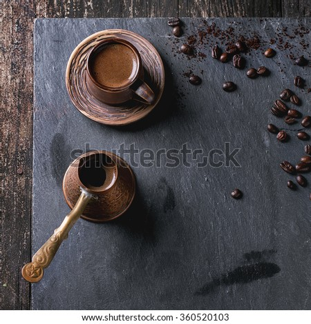 Brown ceramic cup of coffee, old copper cezve and coffee beans. Over black slate as background. With copy space at centre. Top view. Square image