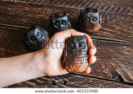 Brown ceramic owls, ceramic owl in the palm, owls family, ceramic owls on a brown background , four ceramic owl - stock photo