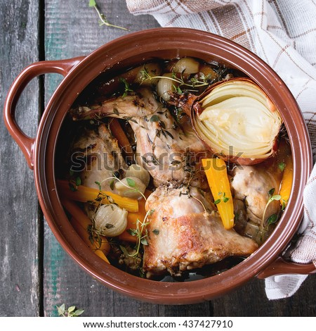 Brown ceramic pot with stewed rabbit with bouillon, vegetables and herbs, served with kitchen towel over old wooden table. Rustic style. Flat lay. Square image