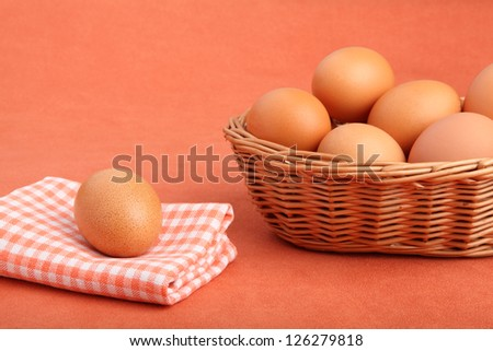 Brown chicken egg on vintage tablecloth and eggs in the basket - stock photo