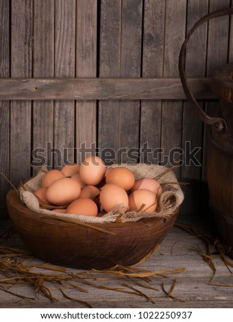 Brown chicken eggs in a wooden bowl with rustic background
