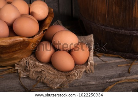 Brown chicken eggs on a burlap cloth and in a bowl in a rustic setting