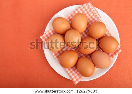 Brown chicken eggs on vintage tablecloth on white plate (from above)