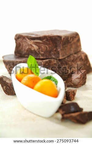 Brown chocolate chunk block and fresh kumquat. This is perfect harmony of tasting flavor chocolate and orange, lemon, exotic for cake, muffin, ice cream, fondue, pie and your favorite desserts.