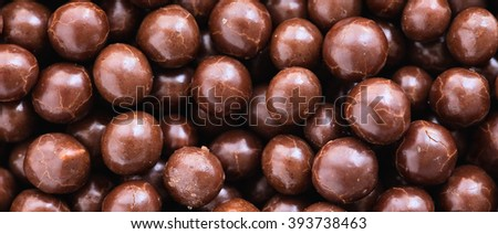 Brown chocolate  dragee balls background, close up, top view, letterbox format