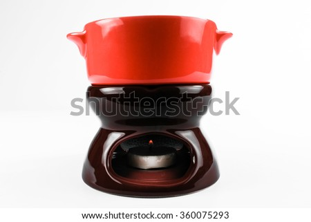 Brown chocolate fondue stove of ceramic with burning candle and red pan on it. Isolate on white background.