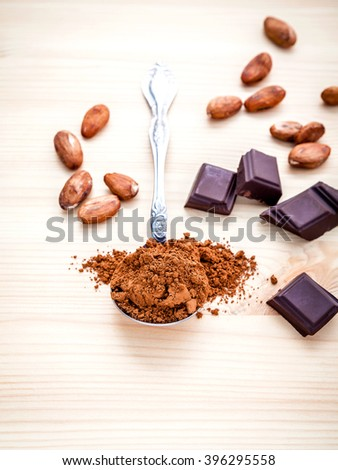 Brown chocolate powder in spoon , Roasted cocoa beans and dark chocolate setup on wooden background. Selective focus depth of field on chocolate powder.
