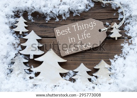 Brown Christmas Label With Ribbon On Wooden  Background With White Christmas Trees And Snow. Vintage Style. Label With English Quote Best Things In Life Are Free For Christmas Or Season Greetings - stock photo
