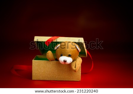 Brown Christmas teddy bear peeking over the edge of a gift box with a loose ribbon isolated against a black and red background - stock photo