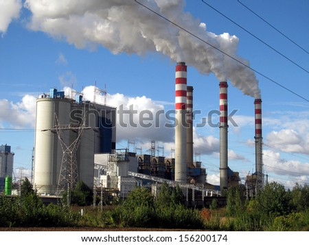 brown-coal power plant with chimney giving off large amounts of gas to the blue sky - stock photo