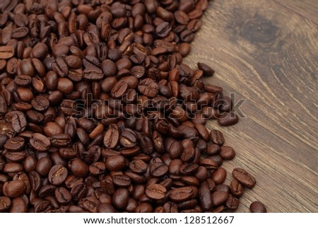 Brown coffee beans, close-up of coffee beans on wood