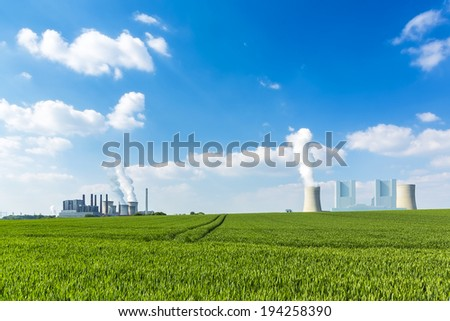 brown cole power plants on agriculture landscape with blue cloudy sky - stock photo