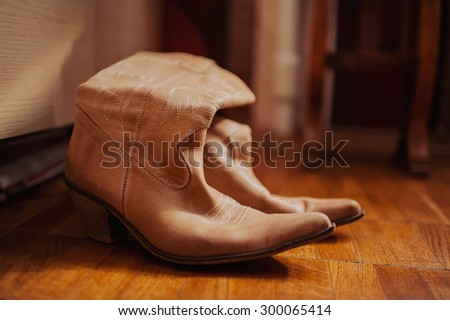 brown cowboy boots on a wooden floor - stock photo
