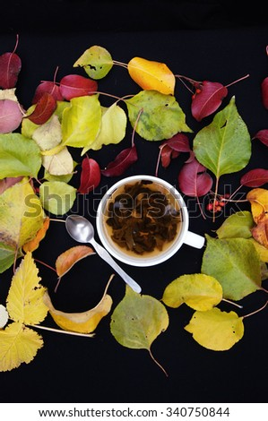 Brown cup with fresh green tea. Cup of tea on a black background,  top view,many  colourful autumn leaves, cup of tea surrounded by autumn leaves. Autumn background. Yellow and green leaves. Herbal  - stock photo