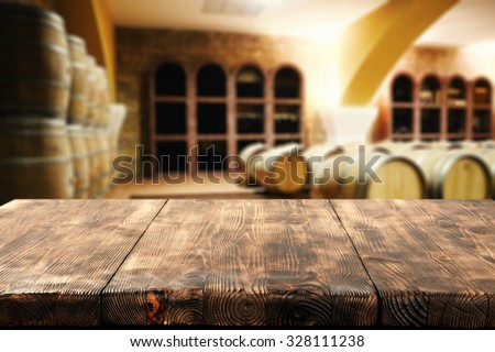 brown dark interior with barrels of wine and worn desk space  - stock photo
