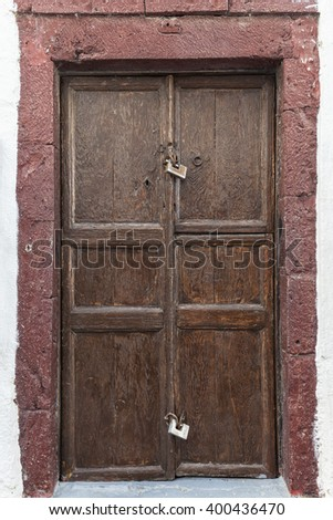 Brown door with red stones in Santorini