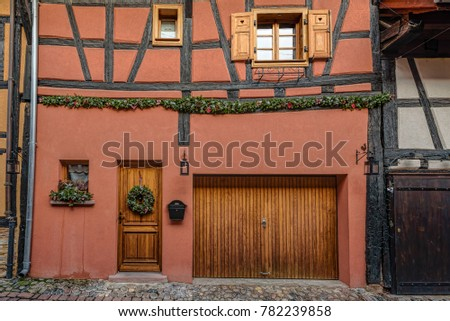 Brown doors and windows on pale creme walls of a small town in French countryside