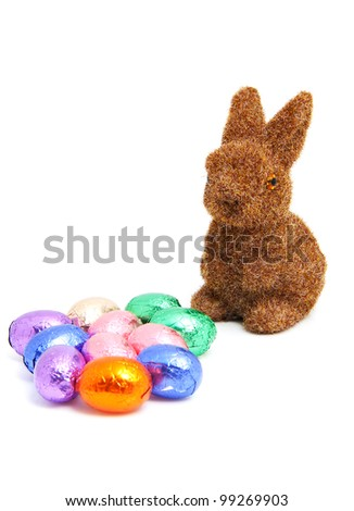 Brown easter bunny and colorful chocolate eggs over white background