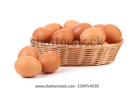 Brown eggs in the basket and near. Isolated on a white backgropund.