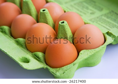 Brown eggs stored in a green cardboard carton