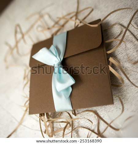 brown envelope with blue ribbon handmade on  shredded paper for Gifting, Shipping - stock photo