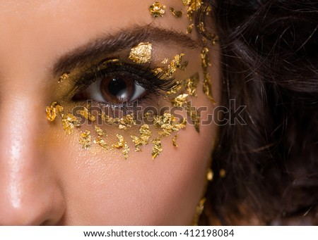 Brown eye in macro surrounded by special golden elements. Cool make-up with black eyeliner, long eyelashes. Cute brunette's curls. Perfect form of eyebrows. Healthy skin.