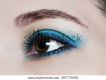 Brown eye makeup in close up. Make up trend: blue shiny eyeshadows. - stock photo